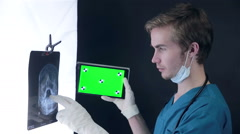 Male doctor examining an x-ray image, using green screen tablet Stock Footage