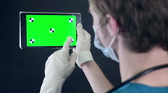 Male doctor holding and browsing digital tablet with green screen Stock Footage