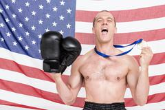 Excited boxer showing his gold medal - stock photo