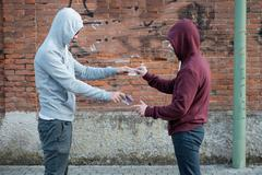 Pusher and drug addict exchanging money and drug - stock photo