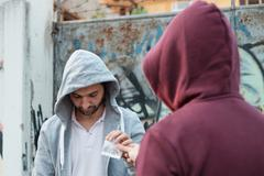 Pusher and drug addict exchanging money and drug Stock Photos