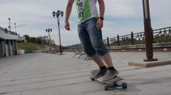 A young guy riding a longboard along the waterfront and makes tricks Stock Footage