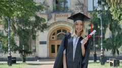 Graduand in Mantle Raises Her Fists Shows Diploma Smiling Standing in Alley Stock Footage