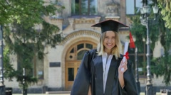 Woman in Mantle Raises Her Hands Shows Diploma Smiling Happy Graduand Standing Stock Footage