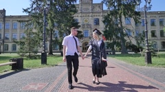 Happy Graduands Couple Walking by Cobblestone Alley at the University Young Stock Footage