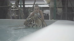 Tourist woman smiling and petting beatiful big tiger lying in the swimming pool Arkistovideo