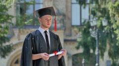 Student in Mantle Has Got His Diploma Thinking Standing in Alley Outside the Stock Footage
