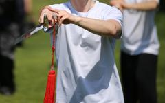 Tai Chi martial arts athlete expert makes motions with sharp sword Kuvituskuvat