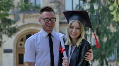 Couple of Happy Graduands Woman Shows Her Diploma Smiling Man in Shirt and Tie Stock Footage