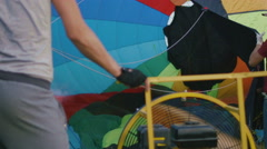 A man inflates the envelope of their hot air balloon on meadow Stock Footage