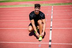 Portrait of male athlete tying her shoe laces on running track Stock Photos