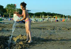 Cute little girl play with bucket and water in the beach in summer Stock Photos