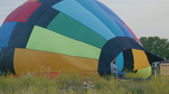A balloon crew inflates the envelope of their hot air balloon - stock footage