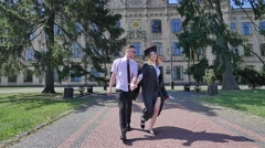 Graduands Having Fun Young Man Twisting a Woman in Mantle Happy Students Stock Footage