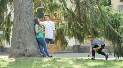 Couple Standing Under Big Tree in Park Teenagers Comes to Scare Their Friends Stock Footage