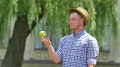 Young Man Throws an Apple up Smells Eats Smiling Outdoors Willow Tree Branches Stock Footage
