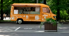 Orange food truck in the park Stock Footage