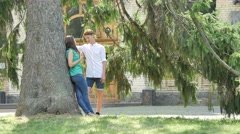 Boy and Girl Standing Under Big Tree in Park Young People Comes to Scare Their Stock Footage