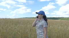 Young pretty farmer girl standing in yellow wheat field and talking on the ph Stock Footage