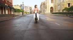 Young beautiful girl riding around city on scooter at sunrise. Slow motion Stock Footage