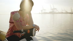 Young beautiful girl sitting on scooter near sea at sunrise. Slow motion Stock Footage