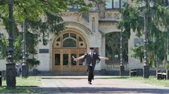 Happy Graduand Jumps Throws Hat up Walking University Courtyard Young Man in Stock Footage