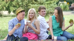 Young People Eating and Drinking on a Lawn Sitting on a Green Grass in Park Stock Footage