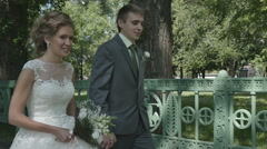 A newlywed couple walk in the Park Stock Footage