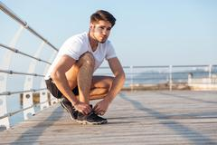 Sportsman laces his sneakers on wooden terrace Stock Photos