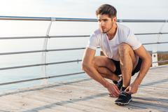 Man athlete laces his sneakers on pier - stock photo