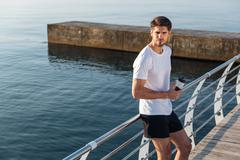 Sportsman standing and drinking water on pier - stock photo