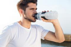 Sportsman in white shirt drinking water outdoors - stock photo
