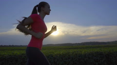 The young woman run on the background of the sunset. Wide angle. Slow motion Stock Footage