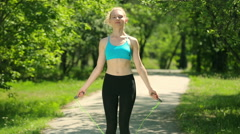 Girl doing a workout outdoors. Girl jumping on jump rope with a smile. Young Stock Footage