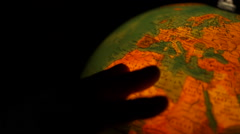 Lit political globe rotating by hand Stock Footage