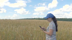 Young pretty farmer girl standing in yellow wheat field  with a tablet in han Stock Footage