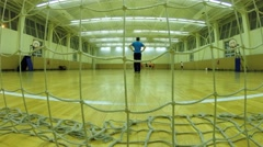Players play football in spacious hall, view through net at the gate Stock Footage