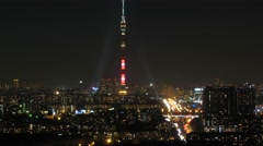 Ostankino Tower in the night sky and illuminated city. Time lapse. Stock Footage