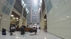 People sit and walk in lobby of business center Preo-8, camera rotate. Stock Footage
