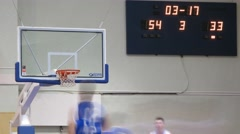 Players playing basketball around the scoreboard Stock Footage