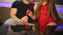 Woman and man sitting at the table and smoking hookah Stock Footage