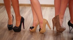 Legs of four women in high-heeled shoes putting their feet on toes Stock Footage