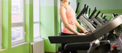 Fitness girl running on treadmill Stock Photos