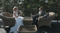 Wedding couple drinking champagne at outdoor cafe on the seafrontthe bride and Stock Footage