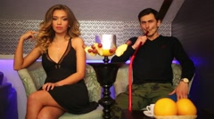 Young beautiful man and woman rest and smoking hookah Stock Footage