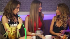 Three girls are sitting in a cafe, talking and smoking hookah Stock Footage