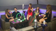 Five young people relaxing together and smoking hookah Stock Footage
