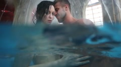 Man and woman embracing under the water jets in the pool Stock Footage