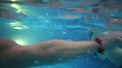 A man and a woman are swimming in blue clear water in swimming pool Stock Footage