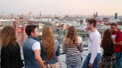 Young people look at the city from the observation deck Stock Footage